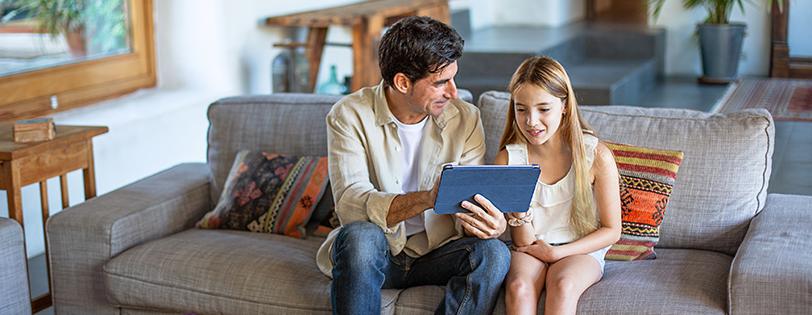 Father helping daughter with tablet