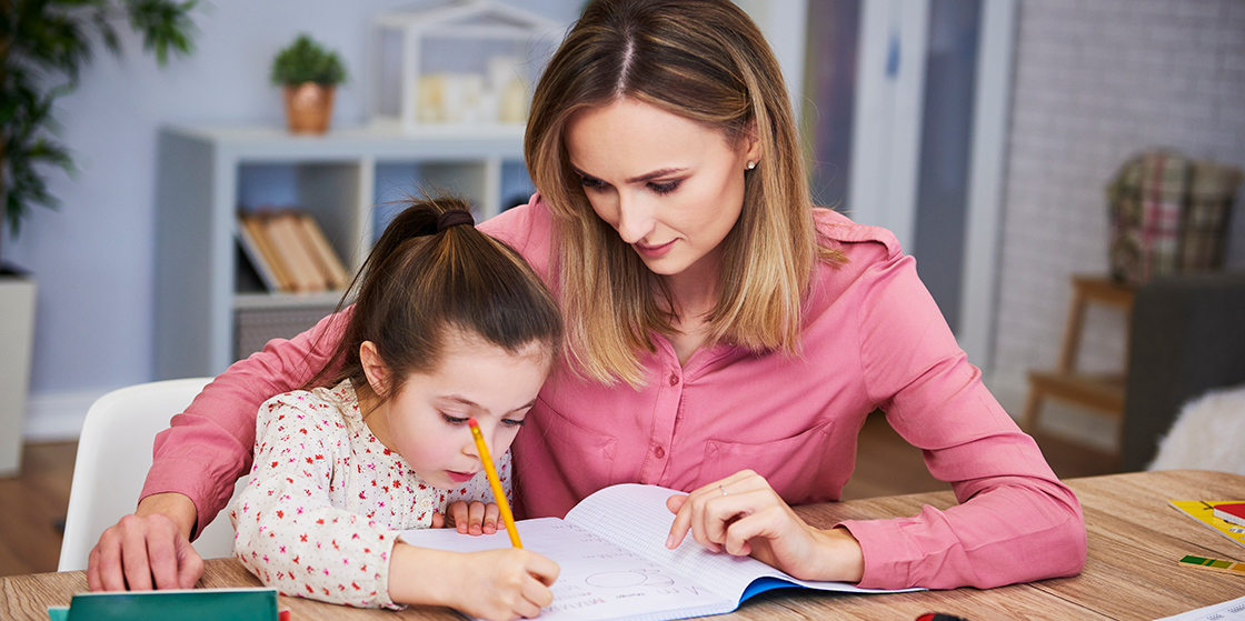 Daughter receiving literacy help from mother at home