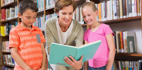 Librarian with two children reading