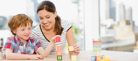 Mother and son at home playing with alphabet blocks.