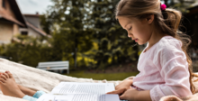 Girl reading outdoors during summer