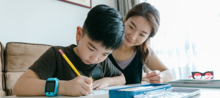 Mother watches as son fills out graphic organizer