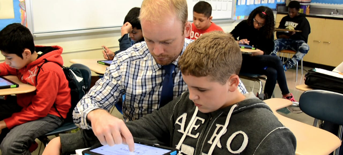 Teacher helping student on tablet