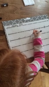 Child writing on calendar