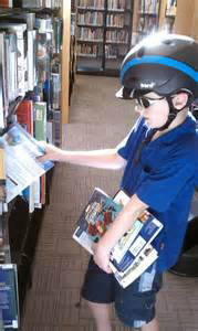 Child picking out books at the library